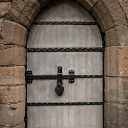 A solid arched doorway at Caernarfon Castle in northwest Wales. A castle originally stood on the site dating back to the late 11th century, but in the late 13th century King Edward I commissioned a new structure that stands to this day. It has distinctive towers and is one of the best preserved of the series of castles Edward I commissioned.