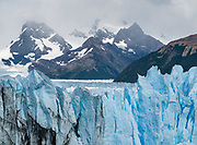 Tall seracs of Perito Moreno Glacier flow from taller Patagonian peaks, near El Calafate, in Santa Cruz Province, Argentina, South America. The spectacular Perito Moreno Glacier is one of 48 glaciers fed by the Southern Patagonian Ice Field (the world's third largest reserve of fresh water). Moreno Glacier melts into Lake Argentino, surrounded by Los Glaciares National Park. Lago Argentino is the biggest freshwater lake in Argentina and reaches as deep as 500 meters (1640 feet). Its outlet, the Santa Cruz River, flows into the Atlantic Ocean. Despite most glaciers worldwide retreating due to global warming, Perito Moreno Glacier has been a relatively stable exception for the past hundred years. Located 78 kilometers (48 mi) from El Calafate, the glacier was named after explorer Francisco Moreno, a pioneer who studied the region in the 1800s and defended the territory of Argentina in the conflict surrounding the international border dispute with Chile. Los Glaciares National Park is honored on UNESCO's World Heritage List.
