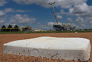 """5/23/04 Firth, Neb.  The bleachers on the softball field at Norris School District 160 near Firth Neb are bent into a metal ball due to a tornado.  Also bats and balls were scattered all over the field.   The school sustained severe damage in Saturday night's tornadoes.  The school, according to Superintendent Roy Baker,  housed about 1,700 students from pre-kindergarten through high school.  The last day of classes was Friday for the students although there were some middle school teachers inside at the time according to Baker. """"The day after the tornado, it's hard to imagine kids coming back on time in August,"""" said Baker. (Photo by Chris Machian/Machian Photo)"""