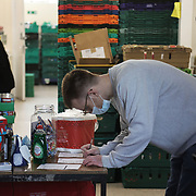 Workers and volunteers at Hackney Foodbank receive and organize food donations, 15th of December 2021, Hackney, East London, United Kingdom. The Hackney Foodbank is part of a nationwide network of foodbanks, supported by The Trussell Trust, working to combat poverty and hunger across the UK. The food bank gives out three days emergency food supplies to families and individual who go hungry in the borrough. The food is all donated by individuals and the food donated is held in a small ware house where it is  sorted and packed for distribution.  More people than ever in Britain have turned to the food bank for help and in Hackney the need has gone up with 350% over the past two years.