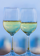 Glasses of wine on a balcony railing against the sky