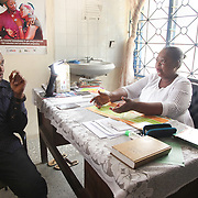 INDIVIDUAL(S) PHOTOGRAPHED: Bridget Agede (left) and Ibiam Azu Agwu (right). LOCATION: Epko Abasi Clinic, Calabar, Cross River, Nigeria. CAPTION: The head doctor at Epko Abasi Clinic gives information about the clinic's operations.