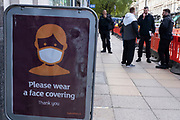 With new local coronavirus lockdown measures now in place and Birmingham currently set at 'Tier 2' or 'high', people not wearing face masks near a face mask sign in the city centre on 14th October 2020 in Birmingham, United Kingdom. This is the first day of the new three tier system in the UK which has levels: 'medium', which includes the rule of six, 'high', which will cover most areas under current restrictions; and 'very high' for those areas with particularly high case numbers. Meanwhile there have been calls by politicians for a 'circuit breaker' complete lockdown to be announced to help the growing spread of the Covid-19 virus.