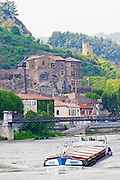 The Chateau de Tournon in the town Tournon and in the background a tower in ruins. Build in the 14th fourteenth and 15th fifteenth century by the Seigneurs de Tournon. The river Rhone and the pedestrian bridge M Seguin, a boat barge on the river.  Tournon-sur-Rhone, Ardeche Ardèche, France, Europe