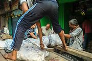 Men unload sacks of onions from a cart, Sitaram Bazar, Old Delhi, India.