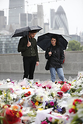 © Licensed to London News Pictures. 06/06/2017. London, UK.         People pay their respects to those who lost their life in a terrorist attack on Saturday evening, after a minutes silence is held outside City Hall, next to a flower tribute in central London. Three men attacked members of the public  after a white van rammed pedestrians on London Bridge. Ten people including the three suspected attackers were killed and 48 injured in the attack. Photo credit: Tolga Akmen/LNP