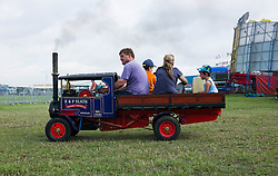 © Licensed to London News Pictures. 01/08/2013<br /> <br /> Pickering, Yorkshire, United Kingdom<br /> <br /> A man drives his family around in their miniature steam truck at the 61st annual Pickering traction engine rally in North Yorkshire. The event has the largest line up of Showman's engines and fairground organs in the north of England and boasts over a thousand vintage and classic cars, commercials, tractors and motorcycles, arena attractions, a fun fair, steam rollers, steam ploughing and along with food and craft marquees the event is the largest event of it's type in the north of England.<br /> <br /> Photo credit : Ian Forsyth/LNP© Licensed to London News Pictures. 01/08/2013