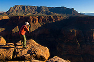 Photographer taking pictures next to edge of canyon cliff, Toroweap, Grand Canyon National Park, Arizona