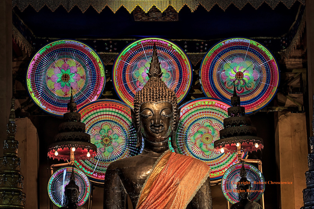 Buddhist Mandela's: A dark Buddhist temple holds a large bronze Buddha statue along with numerous, rotating Mandela's, Wat Mixay, Vientiane Laos.