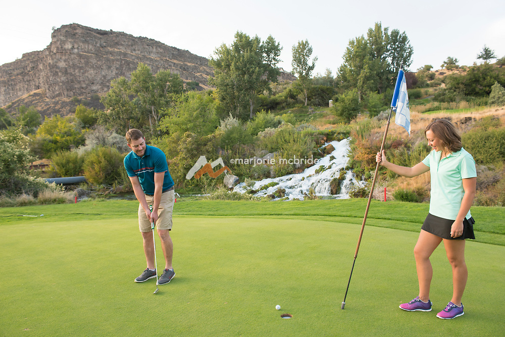 Rudy Ashenbrener left, Sami Ashenbrener right, putting on the 15th green with waterfall and canyon rim beyond at Blue Lakes Country Club in the Snake River Canyon in Twin Falls, Idaho.