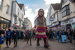 © Licensed to London News Pictures. 21/10/2021. CANTERBURY, UK. A 3.5m tall puppet of a 9 year old Syrian girl called Little Amal, who's travelled 8,000km through Europe from Turkey, After travelling through Folkestone and Dover she is now in Canterbury.She set out from the cathedral and walked through town to the university. Photo credit: Stuart Brock/LNP