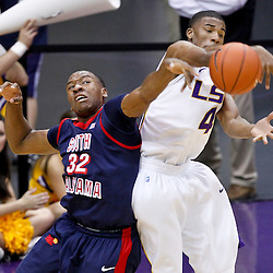 November 23, 2011; Baton Rouge, LA; LSU Tigers guard Chris Bass (4) knocks the ball away from South Alabama Jaguars forward Javier Carter (32) during the second half of a game at the Pete Maravich Assembly Center. South Alabama defeated LSU in overtime 79-75. Mandatory Credit: Derick E. Hingle-US PRESSWIRE
