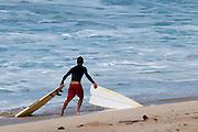 A surfer grabs both halves of his broken surf board.