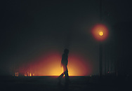 Silhouette of a person crossing the street at night