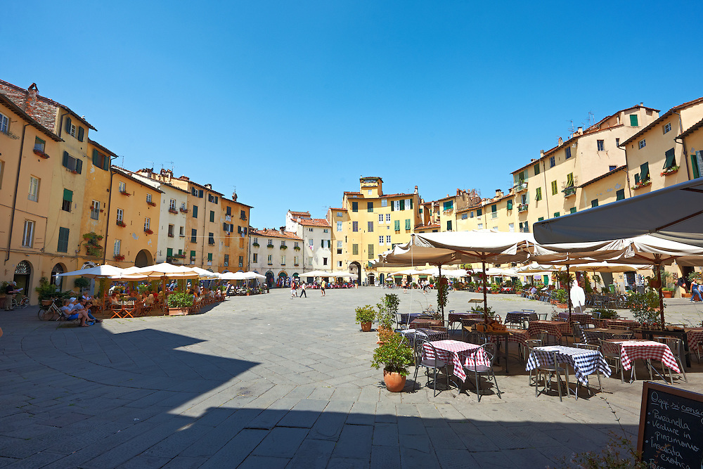Terrace cafe's in the Piazza dell'Anfiteatro inside the ancinet Roman ampitheatre of Lucca, Tunscany, Italy . Piazza dell'Anfiteatro is a public square in the northeast quadrant of walled center of Lucca. The ring of buildings surrounding the square, follows the elliptical shape of the former second century Roman amphitheater of Lucca. The square can be reached through four gateways located at the four vertices of the ellipse. A cross is carved into the central tile of the square with the arms pointing to the four gateways of the square. The base of the former amphitheater  dating back to the 1st or 2nd century BC, at its peak had about 18 rows of amphitheater seats held some 10,000 spectators.<br /> <br /> Visit our ITALY HISTORIC PLACES PHOTO COLLECTION for more   photos of Italy to download or buy as prints https://funkystock.photoshelter.com/gallery-collection/2b-Pictures-Images-of-Italy-Photos-of-Italian-Historic-Landmark-Sites/C0000qxA2zGFjd_k<br /> .<br /> <br /> Visit our ROMAN ART & HISTORIC SITES PHOTO COLLECTIONS for more photos to download or buy as wall art prints https://funkystock.photoshelter.com/gallery-collection/The-Romans-Art-Artefacts-Antiquities-Historic-Sites-Pictures-Images/C0000r2uLJJo9_s0 .<br /> <br /> If you prefer to buy from our ALAMY PHOTO LIBRARY  Collection visit : https://www.alamy.com/portfolio/paul-williams-funkystock/lucca.html .