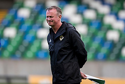 Northern Ireland manager Michael O'Neill reacts to striker Kyle Lafferty placing a cardboard cutout in the dugout during the training session at Windsor Park, Belfast.