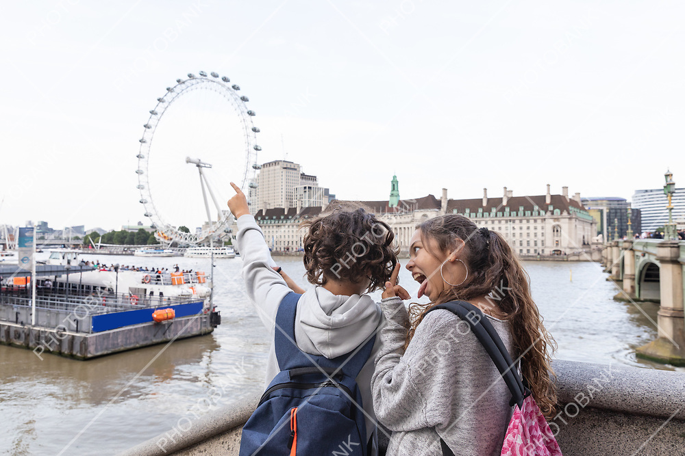 Two young teenagers stand in front of the Thames to indicate the London Eye
