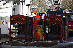 © Licensed to London News Pictures. 16/02/2014. Winchester, Hampshire, UK. Members of Hampshire Fire & Rescue managing the pumps to remove flood water on Park Avenue, Winchester. The pumps are capable of pumping up to 8000 litres of water per minute. Photo credit : Rob Arnold/LNP
