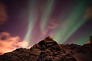 An aurora borealis behind a mountain peak in Andenes.