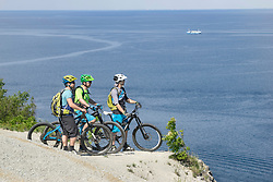 Mature bikers looking at sea while standing at edge of cliff
