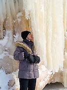 A beautiful woman licks an ice stalactite at the Apostle Island Ice Caves, Makwike Bay, near Bayfield, Wisconsin, on a cold February day.