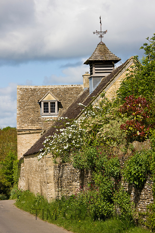 Dovecot and weather vane on period property in Swinbrook, The Cotswolds, Oxfordshire, UK