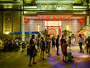 """13 FEBRUARY 2019 - SIHANOUKVILLE, CAMBODIA: People gather in front of the New MGM Casino, a Chinese owned casino in Sihanoukville. There are about 80 Chinese casinos and resort hotels open in Sihanoukville and dozens more under construction. The casinos are changing the city, once a sleepy port on Southeast Asia's """"backpacker trail"""" into a booming city. The change is coming with a cost though. Many Cambodian residents of Sihanoukville  have lost their homes to make way for the casinos and the jobs are going to Chinese workers, brought in to build casinos and work in the casinos.      PHOTO BY JACK KURTZ"""