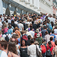 VENICE, ITALY - AUGUST 11:  A large crowd of tourists cross the Ponte della paglia behind St Mark's Square on August 11, 2011 in Venice, Italy. Italian heritage group Italia Nostra warned  that Venice is facing an irreversible environmental catastrophe unless visitor numbers are capped. The acceptable maximum number of tourists for Venice is 33,000. In 2011 the average number of visitors to the city daily is 60,000 that is too high for such a fragile city and is causing the gradual destruction of the lagoon ecosystem.
