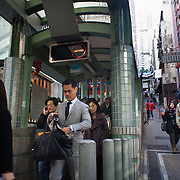 People rush to work down the hill in Mid-levels. Escalators take people down hill in the morning and up hill after 10am. 7 million people live on 1,104km square, making it Hong Kong the most vertical city in the world.