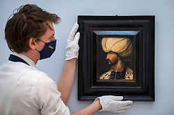 """© Licensed to London News Pictures. 29/03/2021. LONDON, UK. A technician presents """"a newly-discovered 16th/17th-century portrait of Süleyman the Magnificent"""" (est. £80,000-120,000). Preview of the upcoming Arts of the Islamic World & India sale where historic objects, paintings and manuscripts from the last 1,000 years are to be auctioned on 31 March at Sotheby's New Bond Street galleries.  Photo credit: Stephen Chung/LNP"""