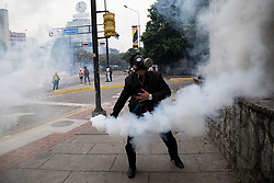 May 8, 2017 - An opposition activist hurls back at riot police a tear gas canister during clashes ensuing a protest against President Nicolas Maduro, in Caracas on May 8, 2017. Venezuela's opposition mobilized Monday in fresh street protests against President Nicolas Maduro's efforts to reform the constitution in a deadly political crisis. Supporters of the opposition Democratic Unity Roundtable (MUD) gathered in eastern Caracas to march to the education ministry under the slogan ''No to the dictatorship. (Credit Image: © Panoramic via ZUMA Press)