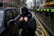 Student wearing balaclava marches against government education cuts in Regent Street. Holding a variety of placards that denounce the coalition government's policy of charging extra higher-education tuition fees, the atmosphere is excited and happy. But tens of thousands of students and school pupils walked out of class, marched, and occupied buildings around the country in the second day of mass action within a fortnight to protest at education cuts and higher tuition fees. There were isolated incidents of violence and skirmishes with police, mostly in central London among the 130,000 students.