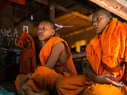 """02 JULY 2013 - ANGKOR WAT, SIEM REAP, SIEM REAP, CAMBODIA:  Buddhist novices at a small monastery near the Bayon temple in the Angkor Wat complex. Angkor Wat is the largest temple complex in the world. The temple was built by the Khmer King Suryavarman II in the early 12th century in Yasodharapura (present-day Angkor), the capital of the Khmer Empire, as his state temple and eventual mausoleum. Angkor Wat was dedicated to Vishnu. It is the best-preserved temple at the site, and has remained a religious centre since its foundation– first Hindu, then Buddhist. The temple is at the top of the high classical style of Khmer architecture. It is a symbol of Cambodia, appearing on the national flag, and it is the country's prime attraction for visitors. The temple is admired for the architecture, the extensive bas-reliefs, and for the numerous devatas adorning its walls. The modern name, Angkor Wat, means """"Temple City"""" or """"City of Temples"""" in Khmer; Angkor, meaning """"city"""" or """"capital city"""", is a vernacular form of the word nokor, which comes from the Sanskrit word nagara. Wat is the Khmer word for """"temple grounds"""", derived from the Pali word """"vatta."""" Prior to this time the temple was known as Preah Pisnulok, after the posthumous title of its founder. It is also the name of complex of temples, which includes Bayon and Preah Khan, in the vicinity. It is by far the most visited tourist attraction in Cambodia. More than half of all tourists to Cambodia visit Angkor.         PHOTO BY JACK KURTZ"""