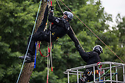 A tree surgeon working with the National Eviction Team removes a Thames Valley police officer from a line which he had attempted to use to reach an environmental activist suspended above the river Colne seeking to prevent the destruction of an ancient alder tree as part of works connected to the HS2 high-speed rail link on 24th July 2020 in Denham, United Kingdom. Officers from the Metropolitan Police, Thames Valley Police, City of London Police and Hampshire Police attended to ensure removal of the tree despite protests by activists.
