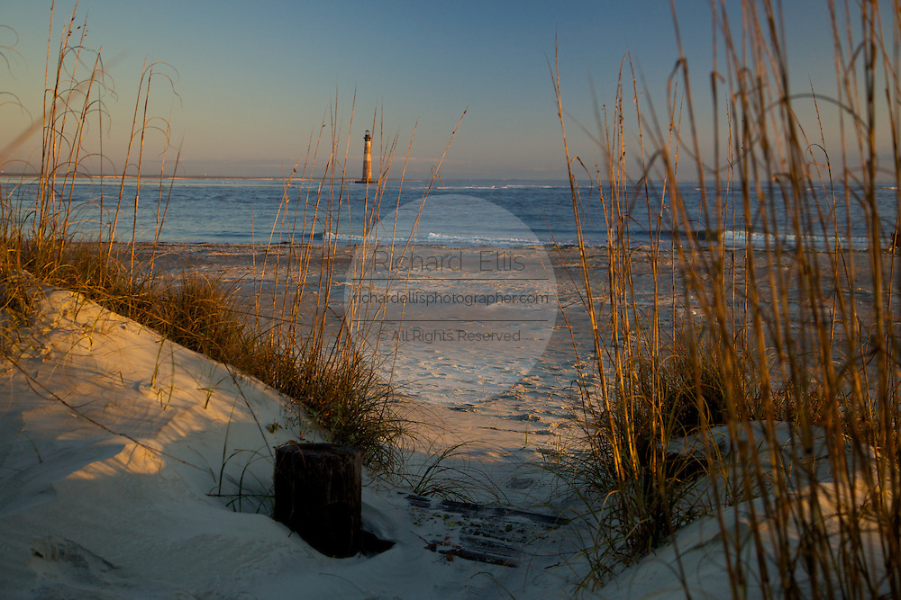 Sunrise over Folly Beach viewing the Morris Lighthouse through the sand dunes near Charleston, SC. Morris Lighthouse dates back to 1767 but was rebuilt in the current form in 1873 after it was destroyed in the civil war.