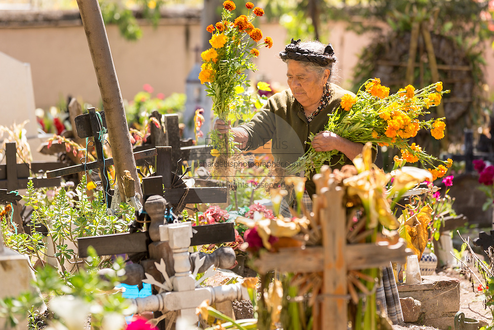 An elderly Zapotec indigenous woman decorates the tomb of family members in a cemetery at the start of the Day of the Dead festival known in spanish as Día de Muertos October 30, 2014 in Teotitlan, Mexico.