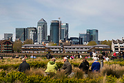 Canary Wharf financial district view from Greenwich in London, United Kingdom. Tourists and visitors to the area relax in the sunshine with this dramatic modern backdrop.