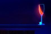 Glass with glowing wine balanced over the edge of a shelf.Black light