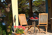 Two teak wooden deck garden chairs on the terrace and a table ready for breakfast. Flowers in pots, red and white geraniums. A table with two red coffee cups Clos des Iles Le Brusc Six Fours Cote d'Azur Var France