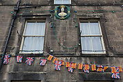 The exterior of the Queens Head pub with Union Jack bunting and the colours of the county of Northumberland, on 25th September 2017, in Rothbury, Northumberland, England.
