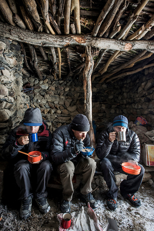 Huddling to eat in a shepherds hut at the 4300m Karabel camp, a semi-nomadic shepherd outpost. Although our expedition was in the summer month of June, a blizzard pinned us down here for a day.