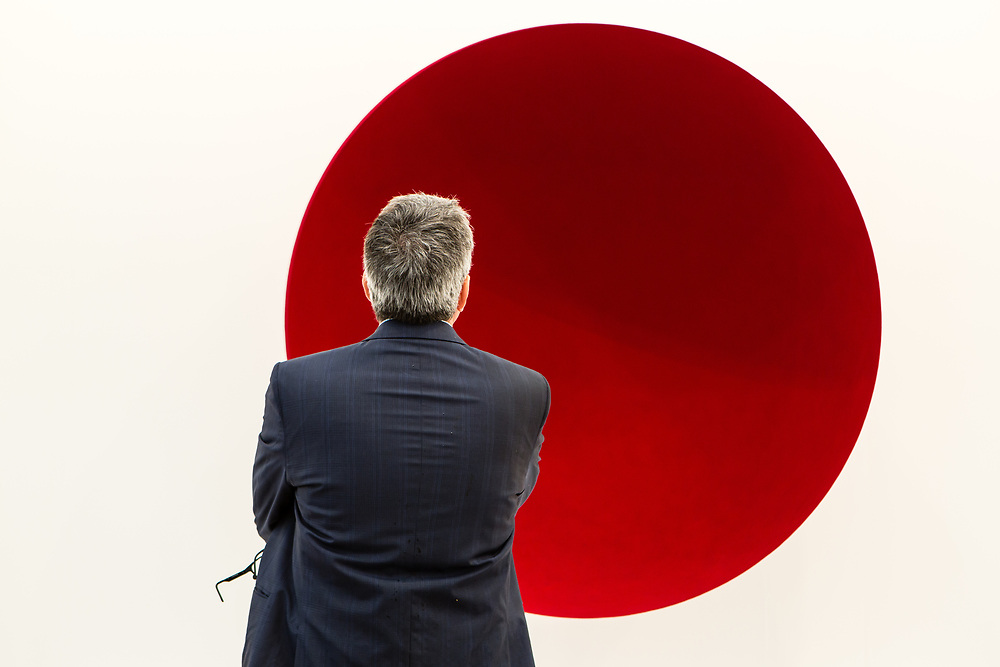 """New York, NY - 5 May 2017. The opening day of the Frieze Art Fair, showcasing modern and contemporary art presented by galleries from around the world, on Randall's Island in New York City. A man looks at Anish Kapoor's fiberglass and pigment """"Void,"""" 1990, in the Lisson Gallery."""