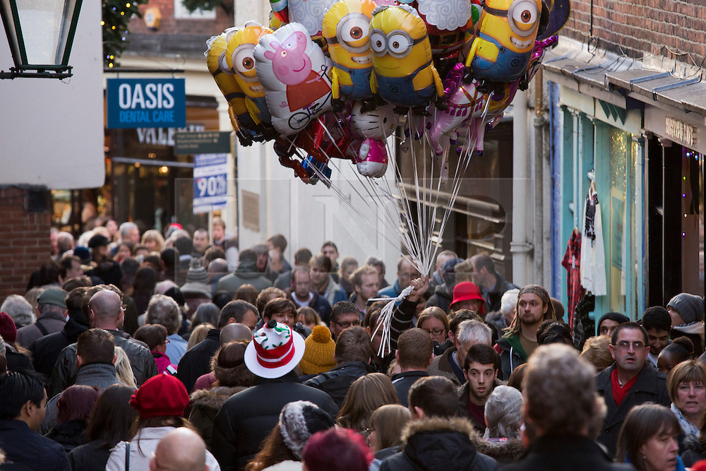 """© Licensed to London News Pictures. 7/12/2013. Lincoln, UK. Lincoln City Centre was packed with Christmas shoppers this weekend. Pictured, a balloon seller struggles to make his way up the """"strait"""" in a busy Lincoln City Centre. Thousands of shoppers filled the City Centre and stewards were called in to direct people up the narrow """"Steep Hill"""" towards the upper area of Lincoln near the Cathedral. Photo credit : Dave Warren/LNP"""
