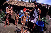 Remedios de la Cruz bathes her young son Merryl, 3 with a bucket of fresh water in Busok Busok fishing village, Aurora province, Philippines