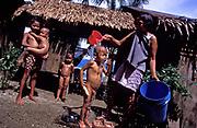 Remedios de la Cruz bathes her young son Merryl, 3 with a bucket of fresh water in Busok Busok fishing village, Aurora province, Philippines