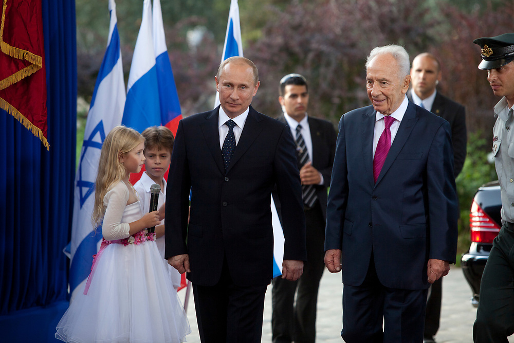 Russian President Vladimir Putin (L) walks with Israeli President Shimon Peres (2nd R) as he arrives for an official welcoming ceremony in his honor, at the President's Residence in Jerusalem, Israel, on June 25, 2012.