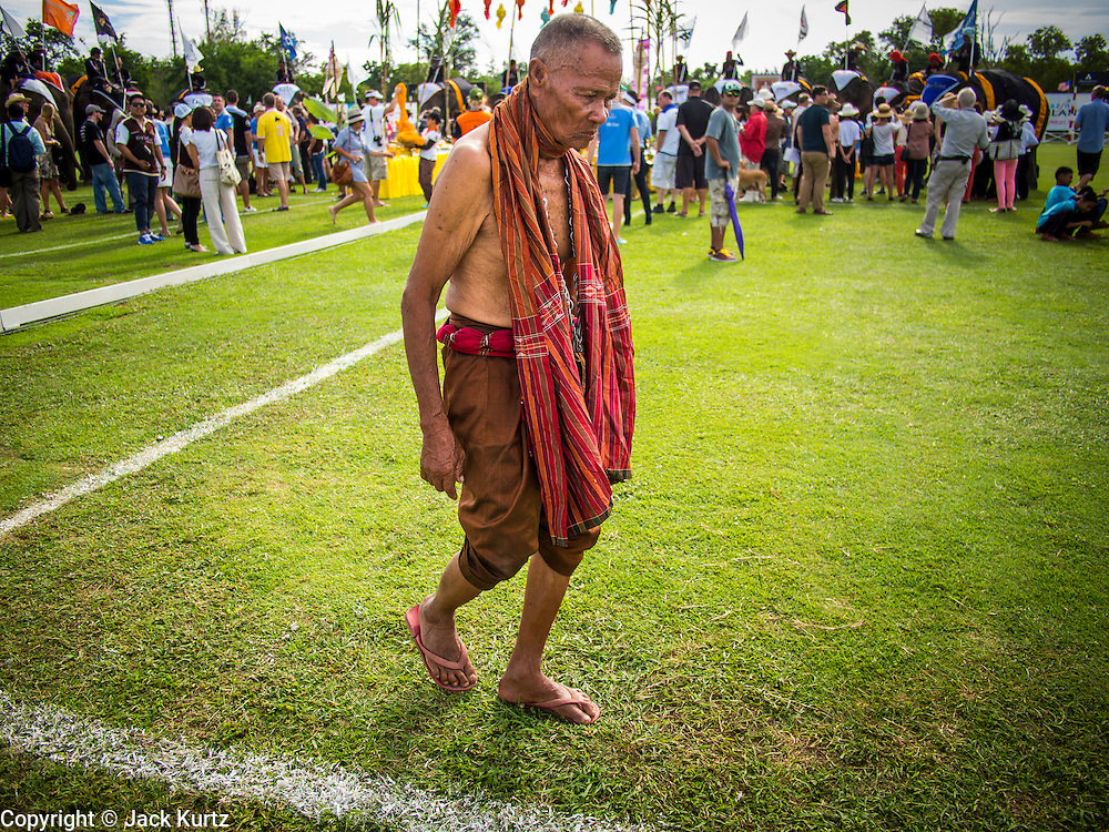 "29 AUGUST 2013 - HUA HIN, PRACHUAP KHIRI KHAN, THAILAND: A ""Khru Ba Yai"" or Elephant Spirit Man, walks off the field after participating in a blessing for the elephants before the King's Cup Elephant Polo Tournament in Hua Hin. The tournament's primary sponsor in Anantara Resorts and the tournament is hosted by Anantara Hua Hin. This is the 12th year for the King's Cup Elephant Polo Tournament. The sport of elephant polo started in Nepal in 1982. Proceeds from the King's Cup tournament goes to help rehabilitate elephants rescued from abuse. Each team has three players and three elephants. Matches take place on a pitch (field) 80 meters by 48 meters using standard polo balls. The game is divided into two 7 minute ""chukkas"" or halves. There are 16 teams in this year's tournament, including one team of transgendered ""ladyboys.""    PHOTO BY JACK KURTZ"