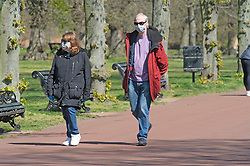 ©Licensed to London News Pictures 14/04/2020  <br /> Greenwich, UK. A man and a woman walking round the park with masks on. Sunny weather in Greenwich park, Greenwich, London as people get out of the house from coronavirus lockdown to exercise. Photo credit:Grant Falvey/LNP