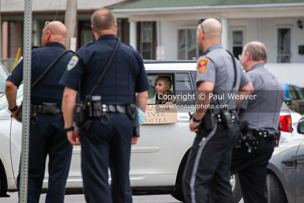 A woman holds a black lives matter sign out the window of a car as it drives by car four cops at a demonstration in Shamokin, PA to protest police violence and racism.