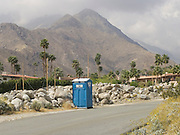 portable toilet along a road against a mountain view
